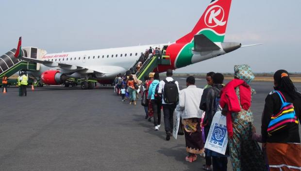 People board plane to be resettled with the help of IOM