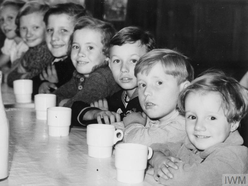 Belgian refugee children waiting for their afternoon tea in London during 1940. Imperial War Museum.