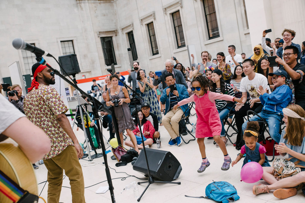 Girl in shades jumps to music at Refugee Week 2017 at British Museum