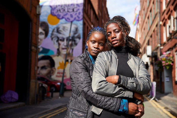 MANCHESTER, 24 July 2017 - Megan Nankabirwa ( blue hair tips) and her partner Lydia Nabukenya in Manchester's gay village. The pair fled Uganda,  where homosexuality is outlawed, after they were discovered to be in a relationship. Christopher Thomond  for The Guardian.