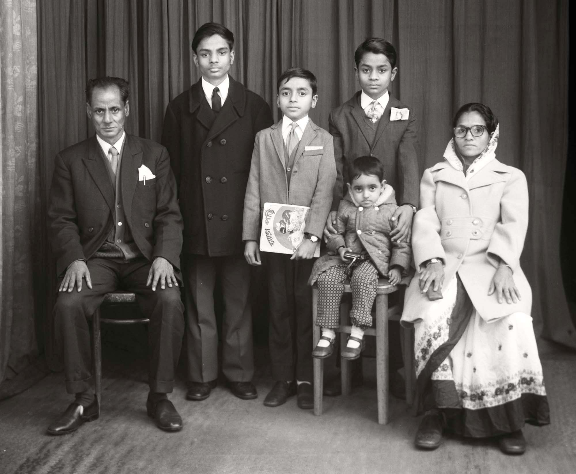 A Bradford Bangladeshi family at the Belle Vue Studio, also known as Sanford Taylor's, who was its original owner. This high street portrait studio on Manningham Lane in Bradford had many customers who moved to the city to seek work during the 1940s, 50s and 60s. It became very popular amongst newly arrived Asian men, who wanted photographs to send home and who were later joined by their wives and children.