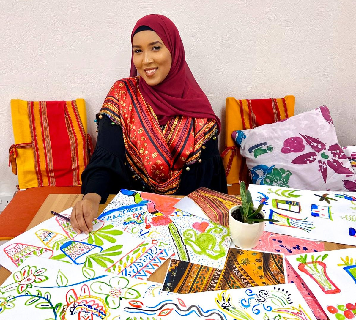 Hafza surrounded by artwork created at one of her workshops
