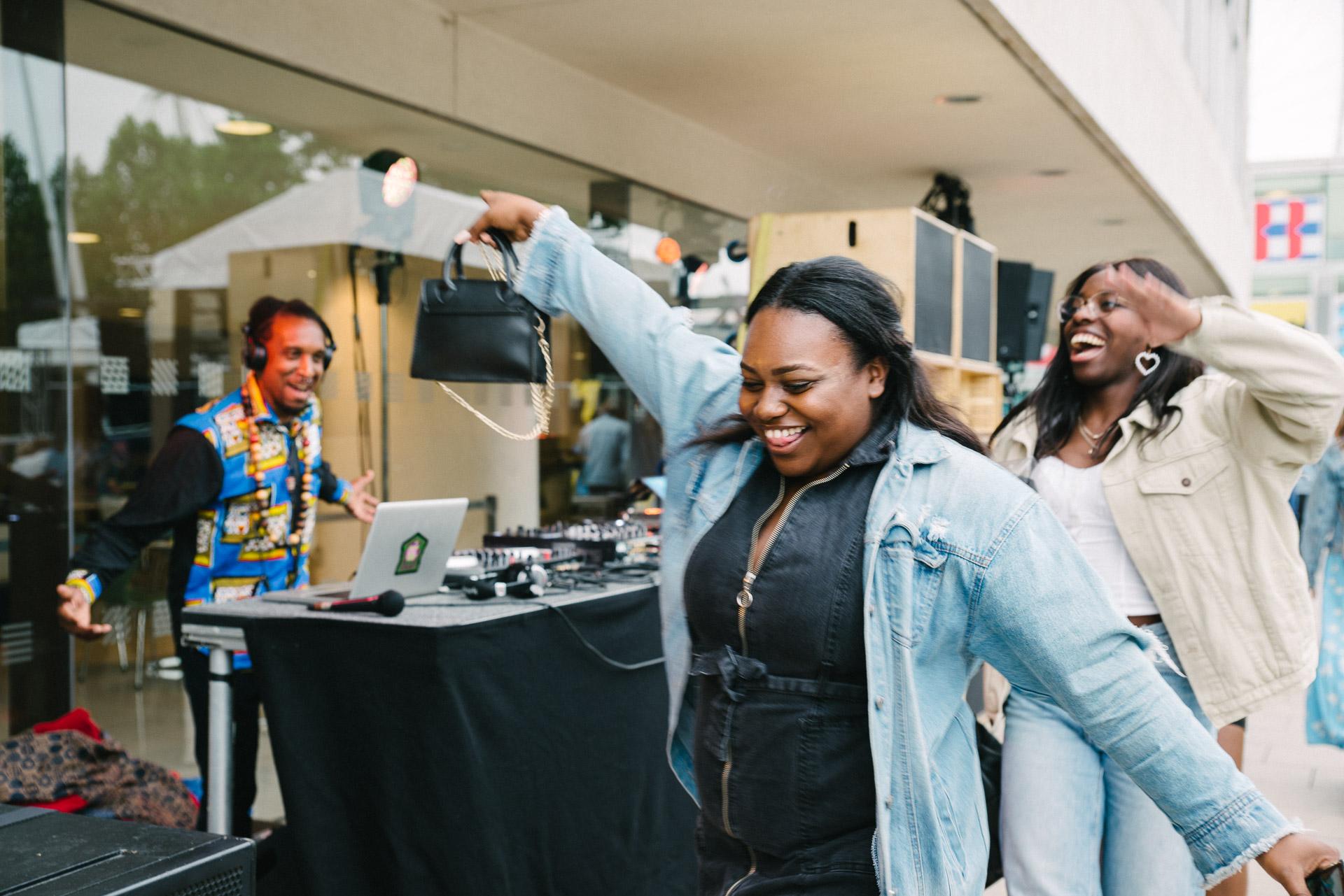 women walk past a DJ smiling and dancing
